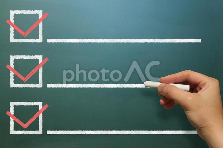 黒板でチェックボックスにマークする男性の手の写真