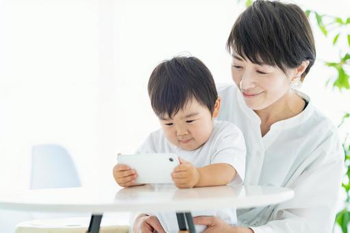 看智能手機屏幕的孩子和媽媽