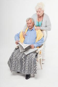 Foreigner senior couple sitting in a chair and reading newspaper 2