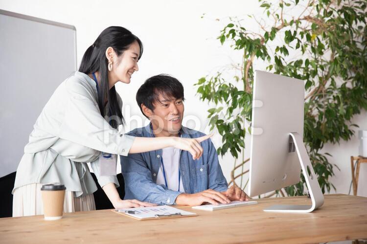 オフィスでミーティングする男女の会社員の写真