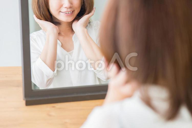 ヘアスタイルを気にする女性(笑顔)の写真