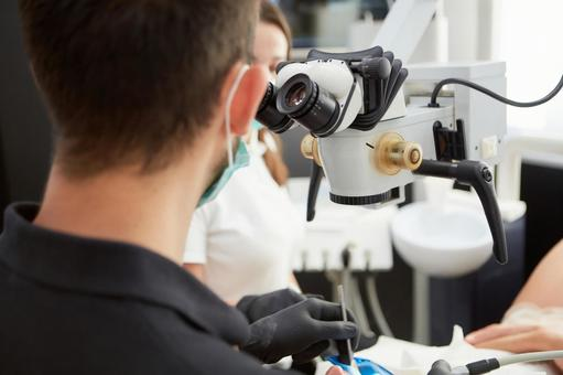 Male dentist with microscope treatment 1