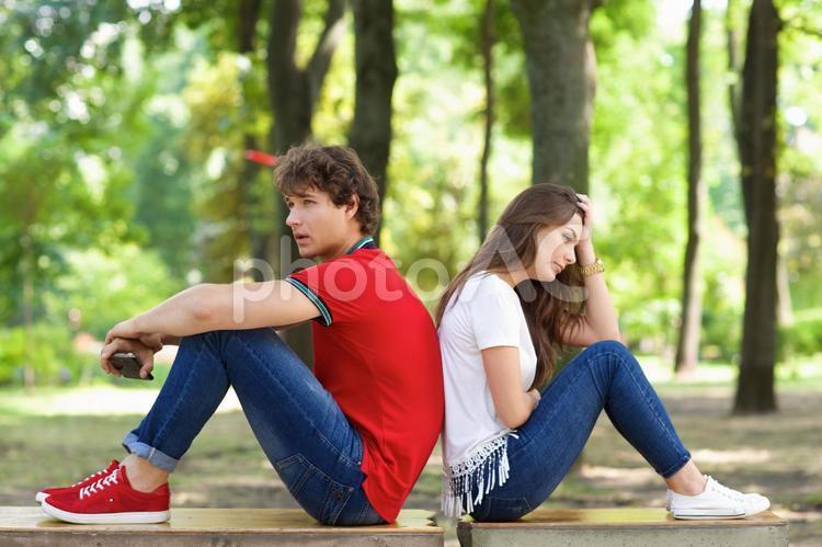 公園にて ベンチに背中合わせに座るカップル5の写真