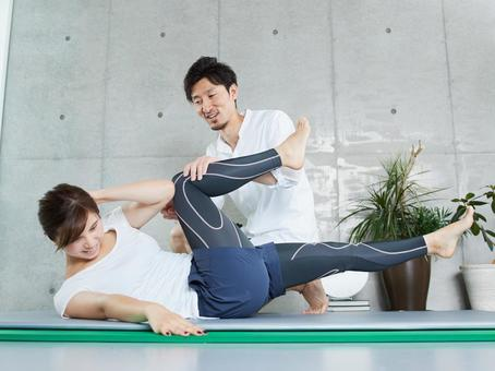 Japanese woman receiving abdominal training from a personal trainer