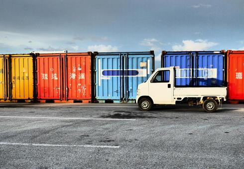 A truck that stops in front of a wharf shipping container