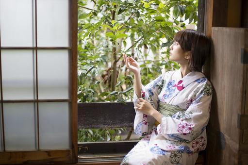 Yukata woman sitting by the window and touching the plants