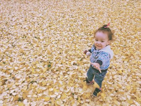 Daughter playing with a carpet of fallen leaves