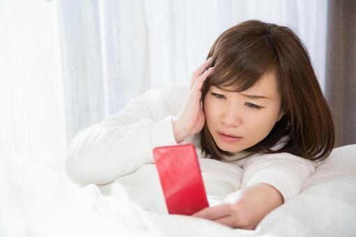 침대에서 스마트 폰을 보는 여자 (곤란)