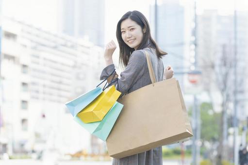 많은 쇼핑백을 안고있는 여성