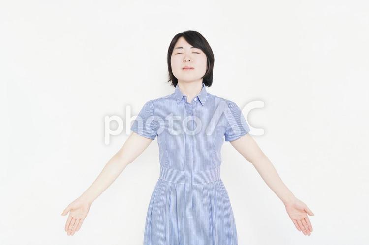 深呼吸をするワンピースを着た女性の写真