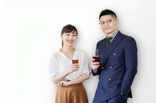 拿著玻璃在交流會和站立帶著微笑的亞裔商人