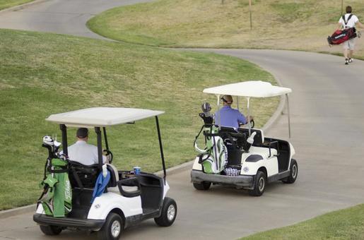 골프 카트로 이동하는 사람