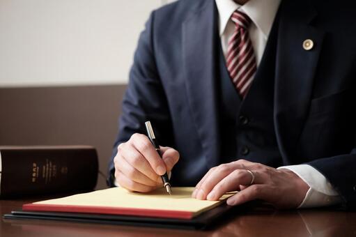 在法律墊上做筆記的男性律師的手