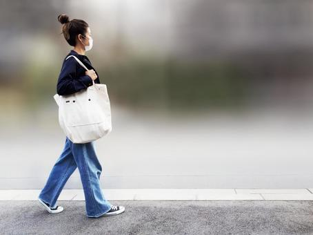 A woman walking with her bag