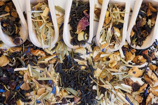 Herbal tea leaves and wooden spoon that fill the screen