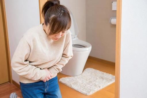A woman crouching in front of the toilet