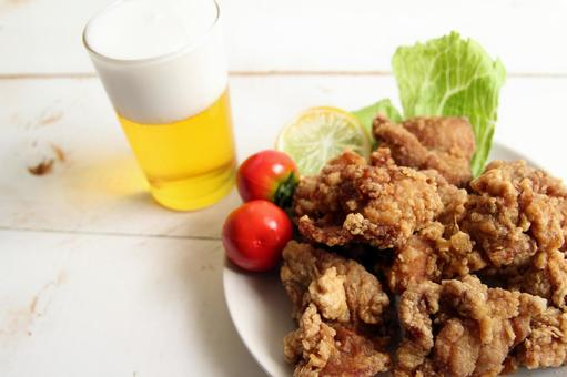 Karaage and beer decorated with cherry tomatoes, lemon and lettuce placed on a white wooden table