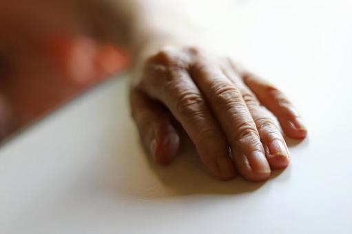 Hands of an elderly woman lying on a nursing bed and placing her hand on the nursing table