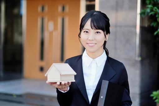 집의 모형을 가진 부동산 가게의 여직원 1