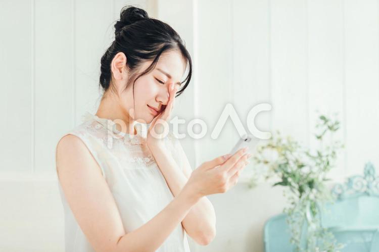 スマホを見て悩む女性(体調不良)の写真