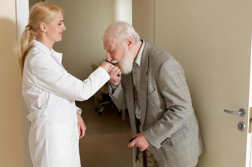 열린 문 앞에서 외국인 여의사의 손에 키스를하는 외국인 노인 남성