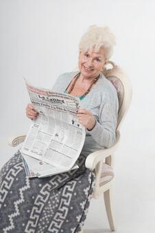 國外老年婦女4讀報紙坐在椅子上