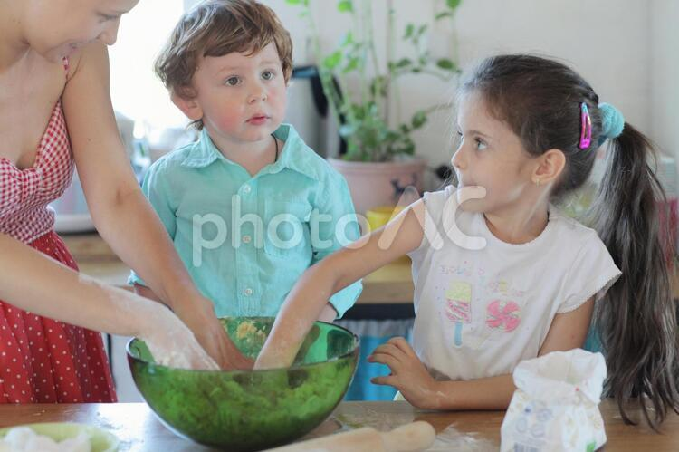 台所で料理の手伝いをする子供たちと母親2の写真