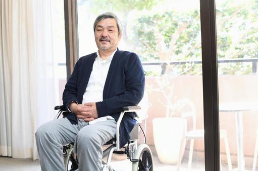 A smiling senior man in a wheelchair