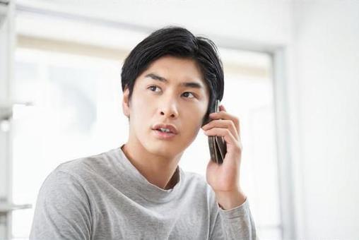 スマートフォンで通話をする日本人男性