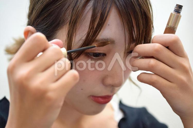 アイブロウマスカラを塗る女性の写真