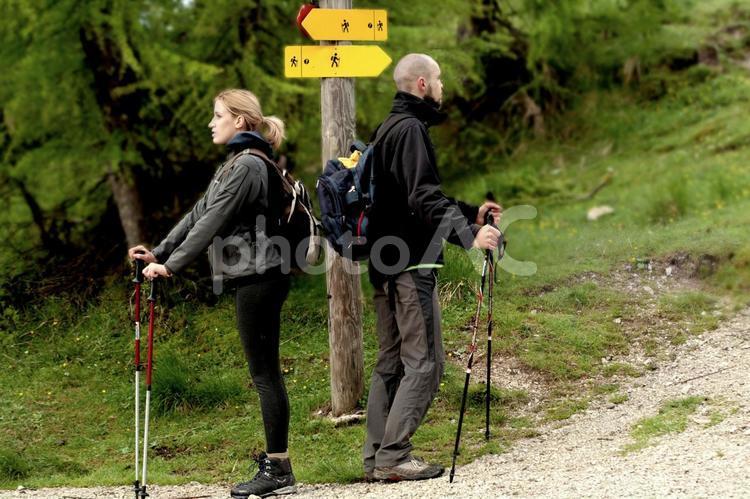 山道の岐路に立つ男女のトレッカーの写真