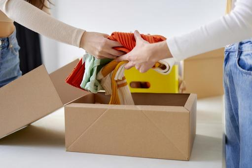 Volunteer woman packing clothes in cardboard