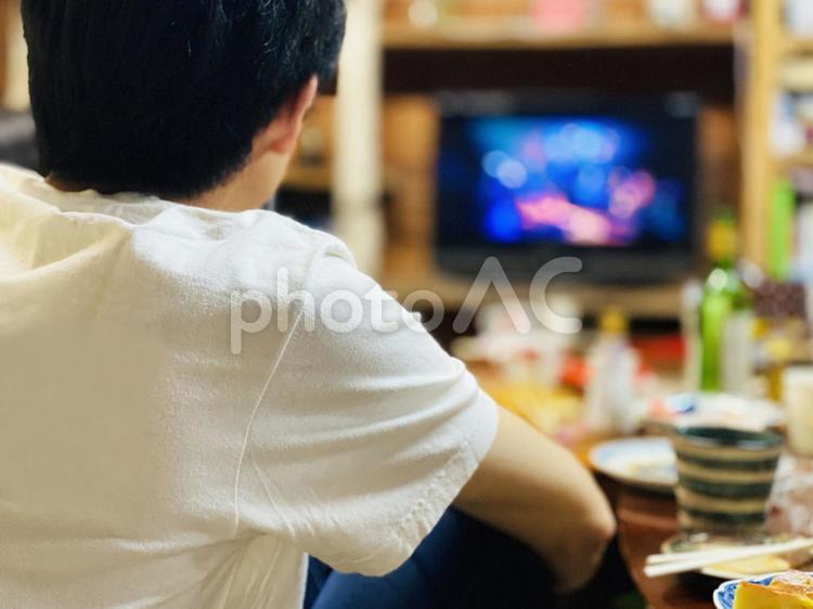 食事しながらテレビでライブを見る男性の写真
