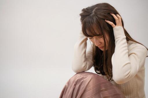머리를 안고 고민하는 여성