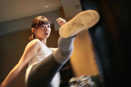Asian woman doing kickboxing training