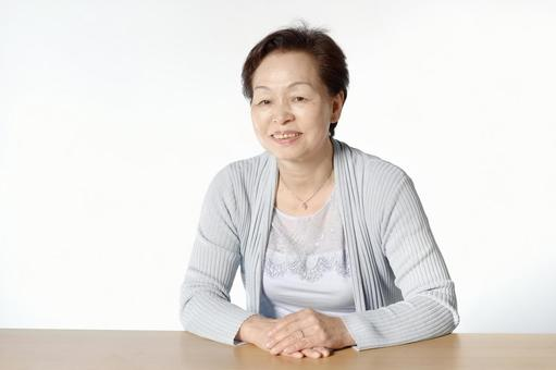 Senior woman sitting in front of the table 1
