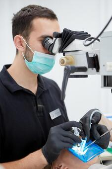 Male dentist with microscope treatment 3