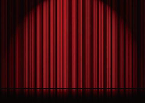 Spotlighted stage and red curtains