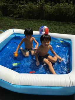 Brothers playing in the plastic pool