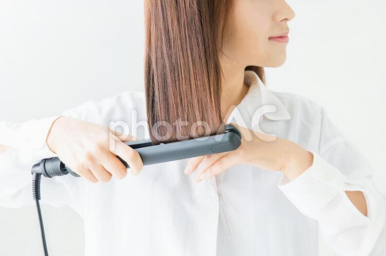 ヘアアイロン(コテ)を使う女性の写真