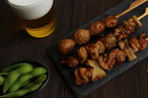 Edamame, yakitori set and beer placed on a wooden table