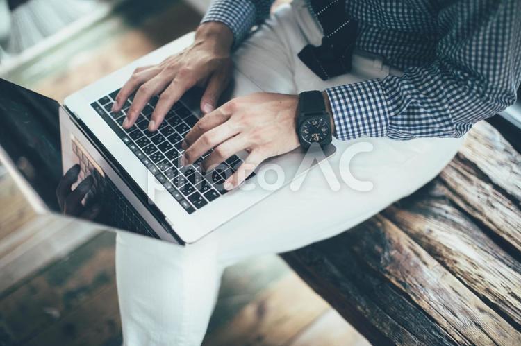 ベンチでノートパソコンを使う会社員の男性4の写真