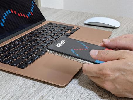 FX investment operation with a smartphone in front of a personal computer