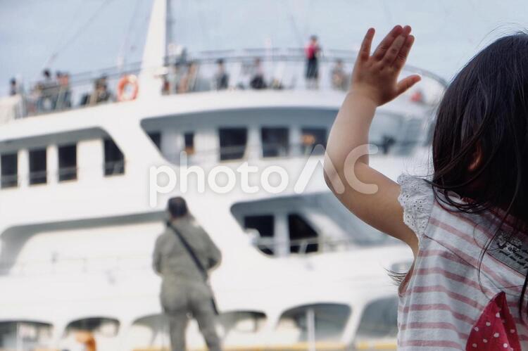 船を見送る子供の写真